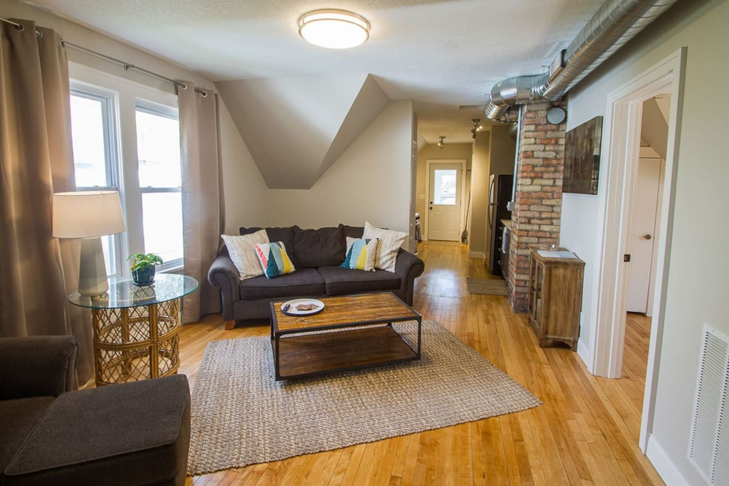 Beautiful exposed brick and duct work above refinished maple floors give the open concept living room and kitchen a modern industrial feel