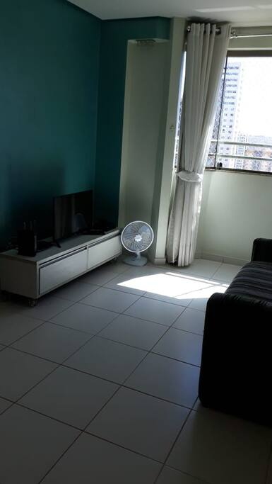 Sala com sofá cama, mesa, rack, TV, cortinas
