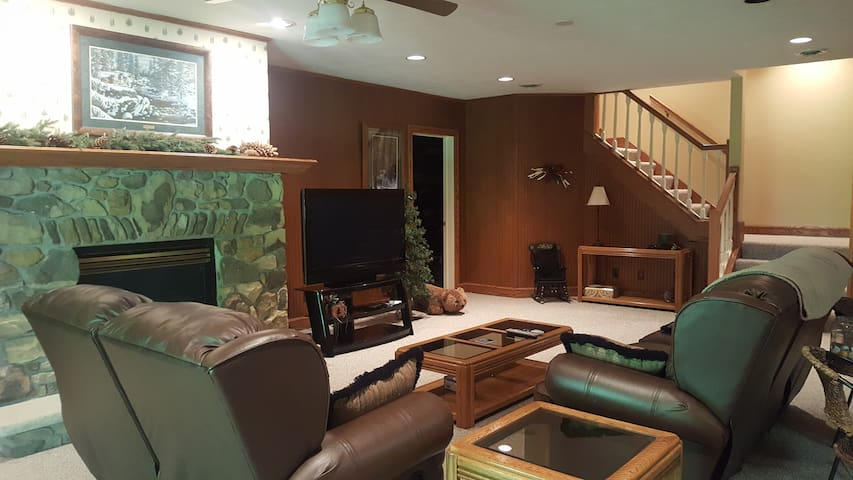 Family room with reclining leather sofas, big screen TV and fireplace.
