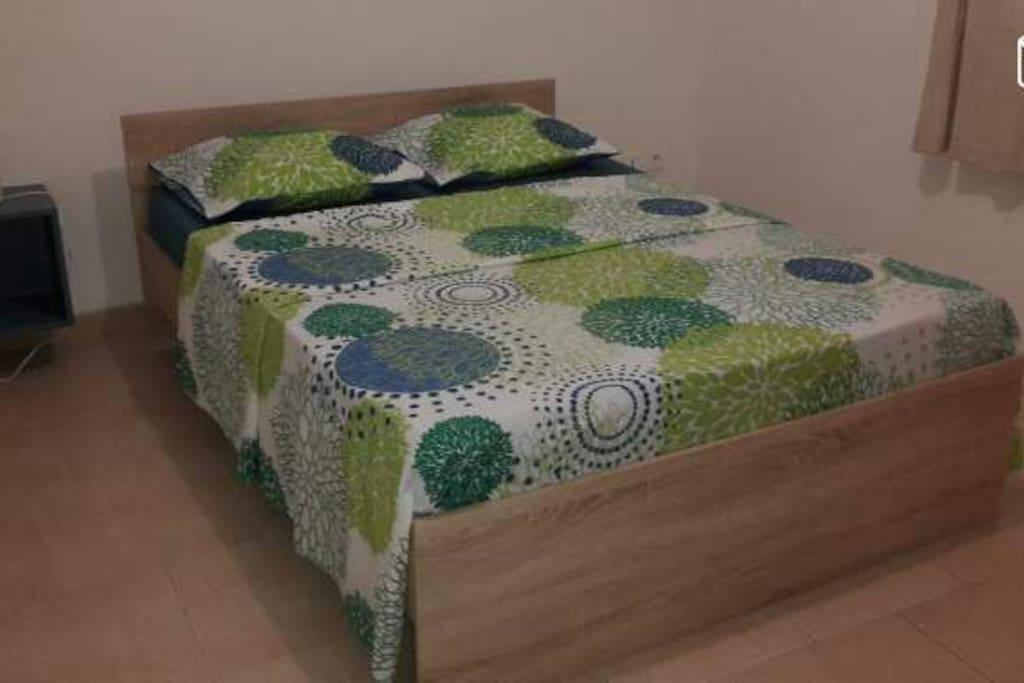 Une chambre composée d'un grand lit, d'une armoire et d'une table de chevet avec lampe;linges de maison et draps de bain fournis