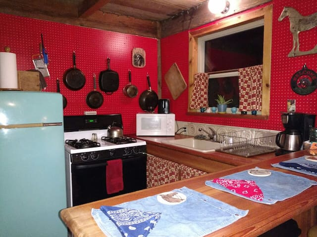 Kitchen with island and two saddle seat chairs, propane stove/range, 50's fridge, sink w/soap dispenser and drying rack, all cook and serve ware, microwave, toaster and coffee maker.