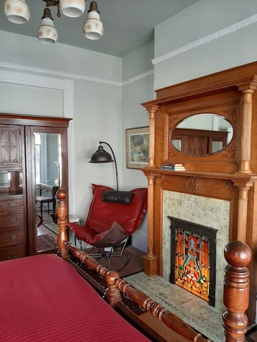 Your room showing (faux) fireplace and comfy reading area with Howard Elliot chair.