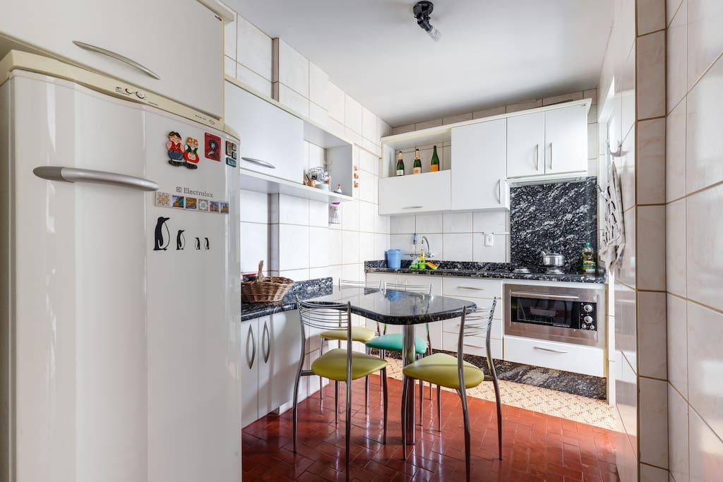 Cozinha equipada com forno, fogão, geladeira, liqüidificador, cafeteira e outros utensílios.