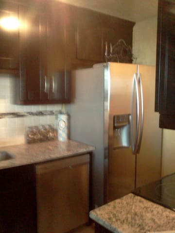 Full size Stainless Steel fridge and dishwasher, granite countertops, Espresso cabinets.
