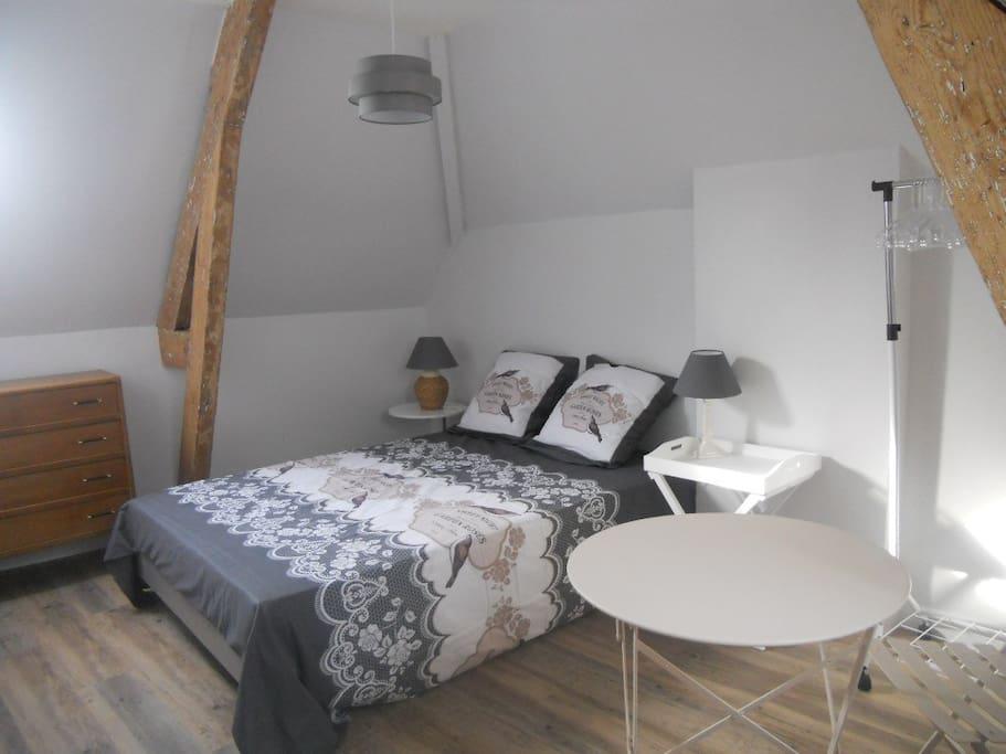 La chambre, avec lit de 140, portant et porte-manteaux, commode à tiroirs, petite table ronde et 2 chaises assorties.