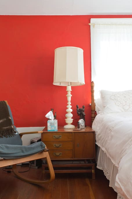 Bedside table, lamp, and rocking chair on left side of bed.