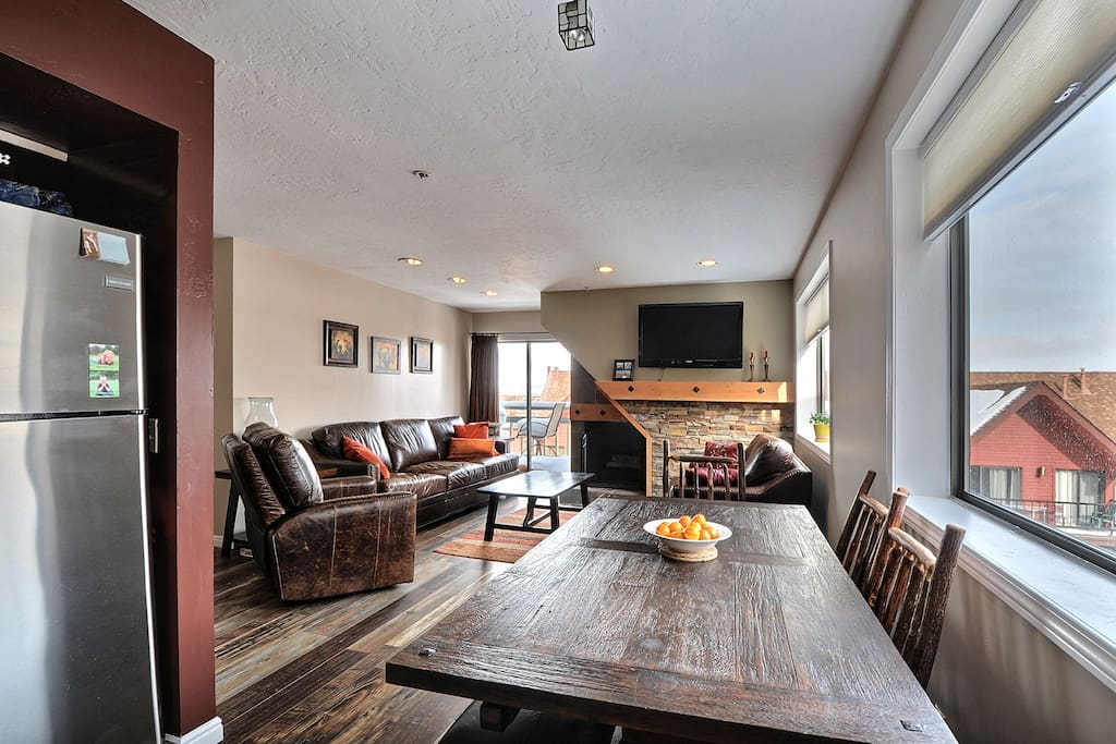 Large family room with fireplace, kitchen, dining area and balcony