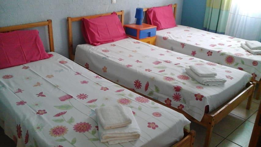 quarto com três camas de solteiro
