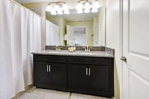 The master en suite bathroom offers tiled floors, mirrored vanity unit with two sinks, toilet and shower/tub combination.