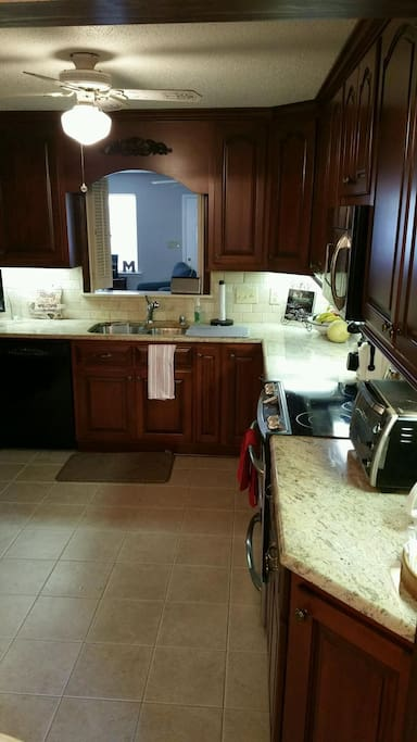 Beautiful Gourmet Kitchen with custom cabinets, granite countertops, tile floor & stainless appliances.  Includes cookware, glassware, dishes, and utensils. (View 1)