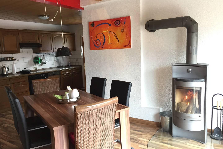 Essecke mit Schwedenofen und Blick in die Küche