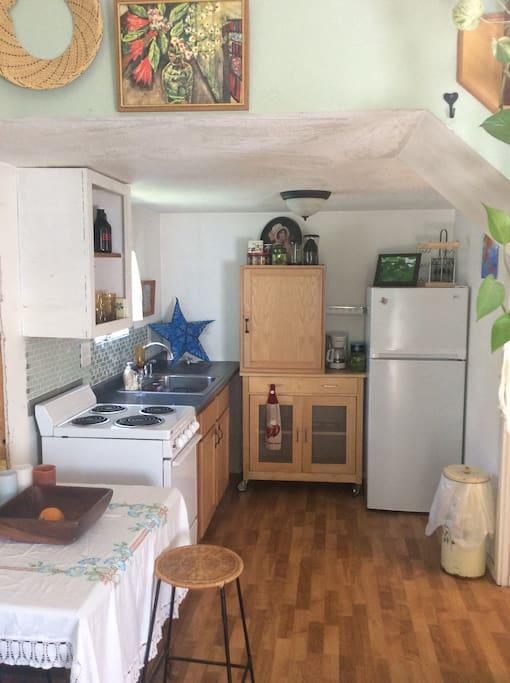 Open kitchen w/ stove, sink, full fridge