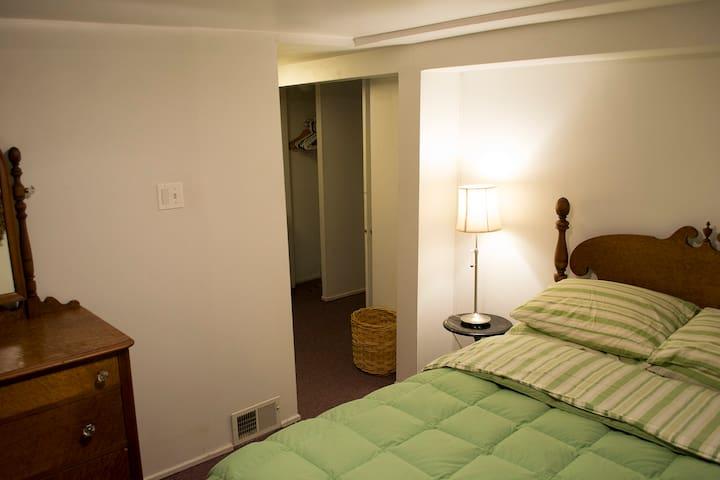 Basement bedroom with Full size bed & antique maple furniture - has en suite bathroom.