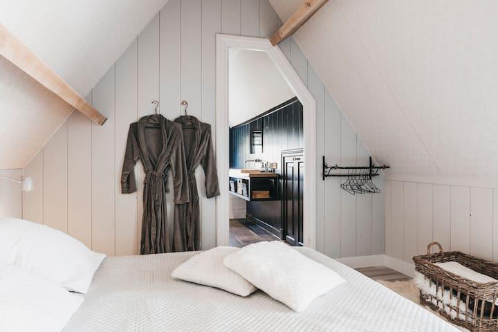Slaapkamer 1 met twee persoons bed en TV
