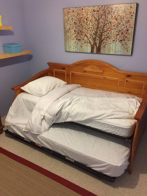 The bed is a high-rise with an additional pull-out mattress underneath for a second guest .