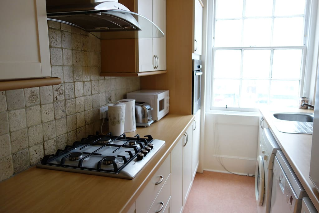 Kitchen with all appliances, including dishwasher, washing machine, microwave, oven, fridge, freezer.