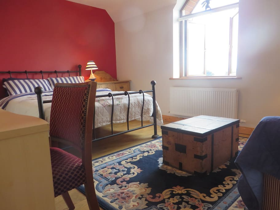 Bedroom with double and pull out double bed, desk and walk in wardrobe.
