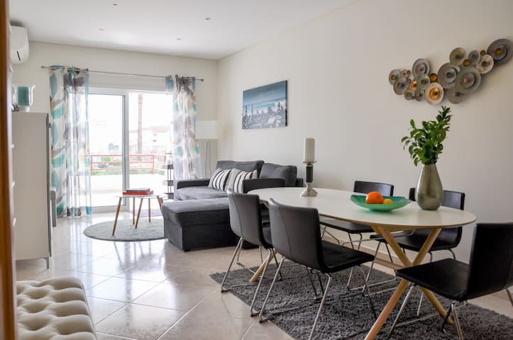 The living room features a comfortable seating area and a dining area with space for up to 6 people. The spacious terrace can be easily accessed through the living room