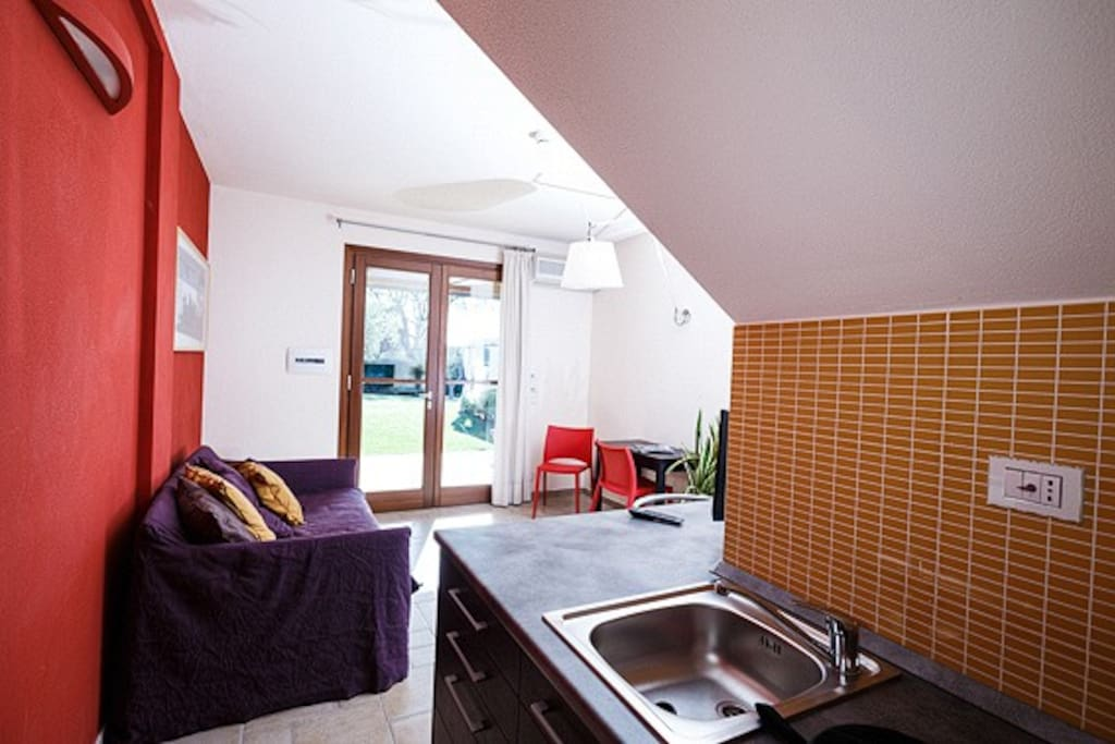 Zona soggiorno con divano letto matrimoniale e angolo cottura