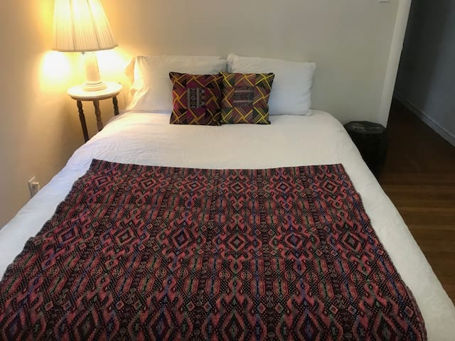 The cozy bedroom features a queen bed with a very firm mattress.