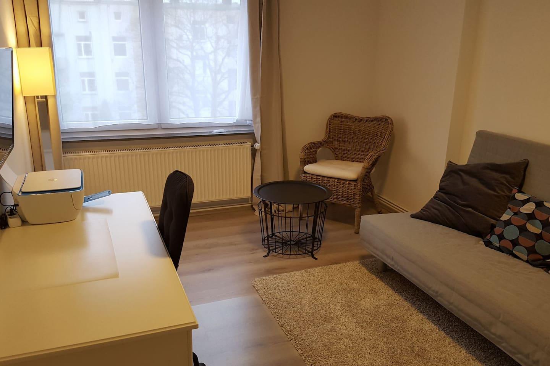 Wohnzimmer mit TV, Drucker, Schlafsofa, Schreibtisch