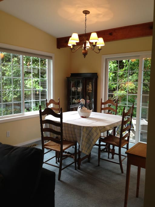 The dining room is full of light with view of the yard and gardens.