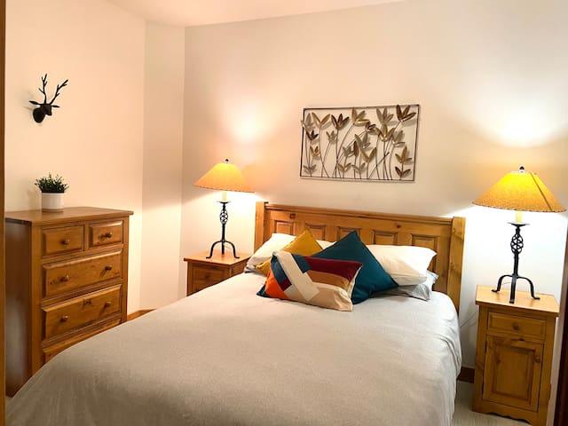 Third bedroom with queen bed, closet and dresser.
