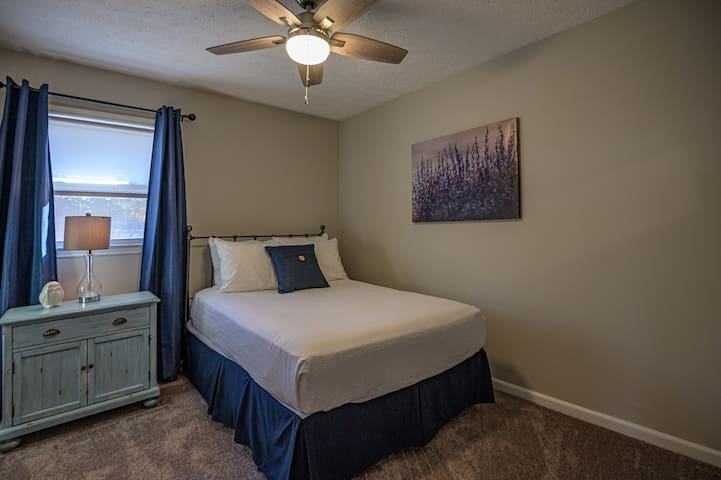Guest bedroom with full size bed and ceiling fan.