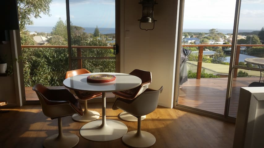Living/dining opening to decking area with views overlooking the cape.