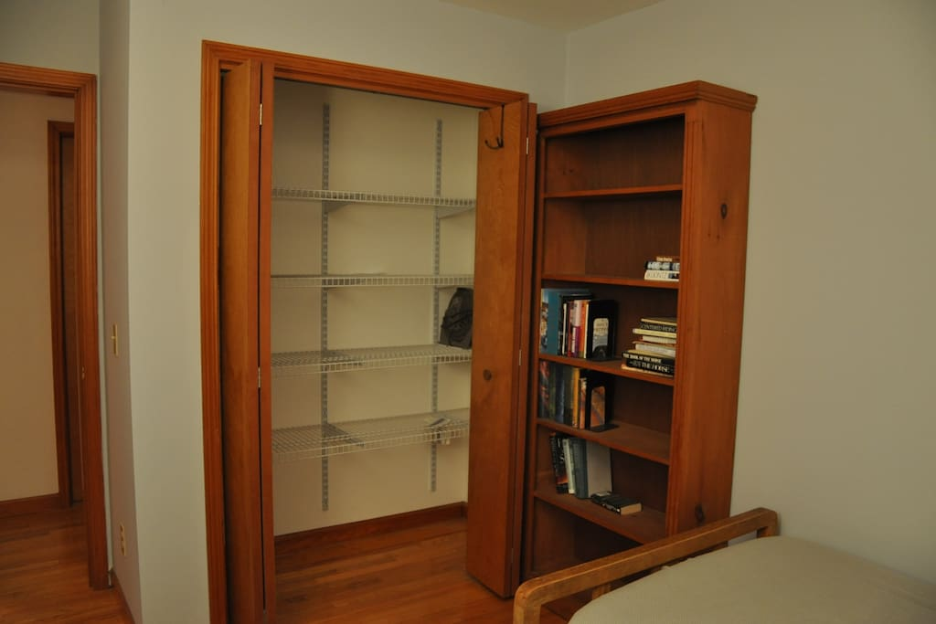 A full closet has lots of shelving & the room also has a dresser