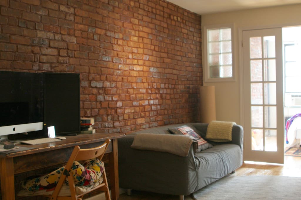 A cozy livingroom with exposed brick