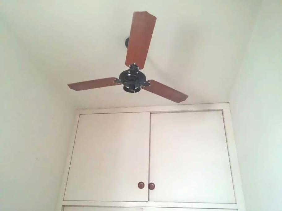 The room has a ceilimg fan, O quarto possui ventilador de teto.
