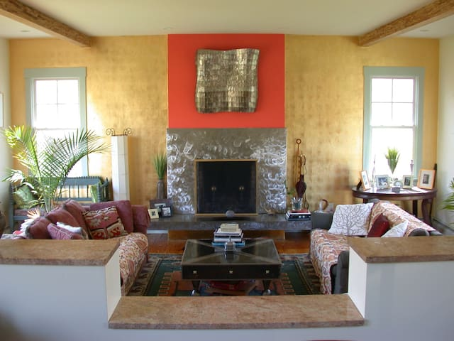 Cozy, elegant, art appointed living room. Two steps down.French doors on both sides.