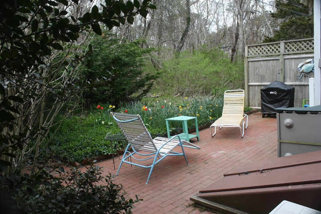 Patio with retractable awning, furniture, & gas grill.
