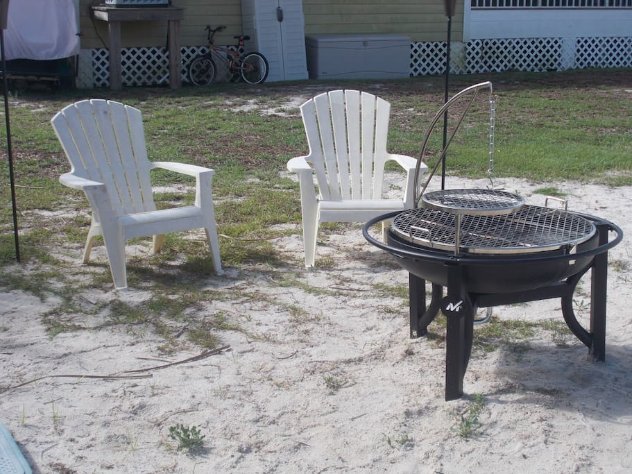 Tiki torches, chairs, cowboy grill and regular grill await you