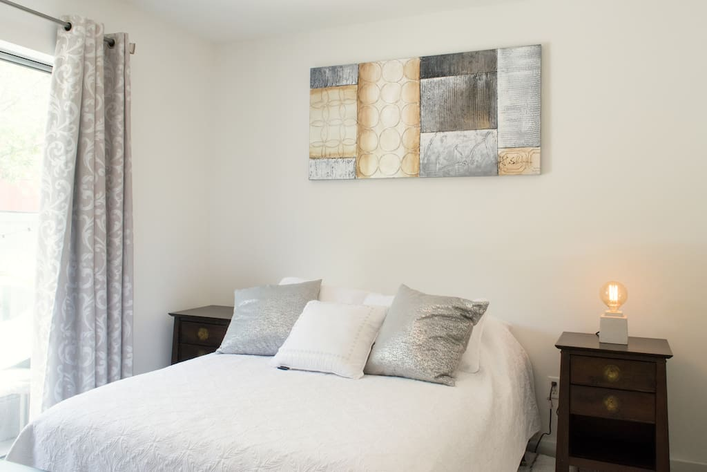 Private bedroom on first floor of townhouse with full size bed, dresser and bed side tables, Apple TV and direct access to patio and private bathroom