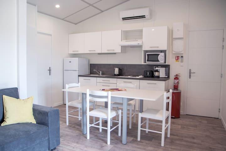Espace cuisine ouvert sur le séjour. Cuisine équipée d'un micro-onde, grille-pain, frigo et congélateur, cafetière Nepresso, bouilloire, plaque de cuisson, hotte, vaisselle
