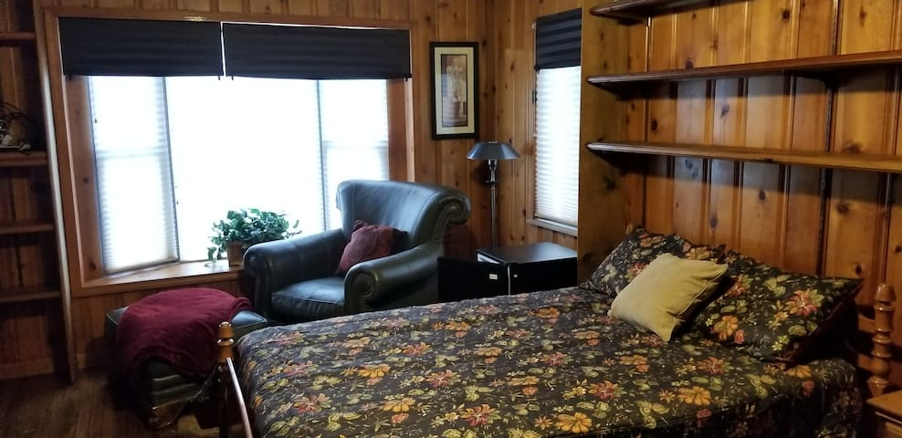 This bedroom is 1 of the largest rooms with a hardwood floor, lots of wall shelving for storage, full size comfy bed with memory foam topper, mini fridge, flat screen TV, chair, ottoman, reading lamp, nightstand, storage drawers & full length mirror.