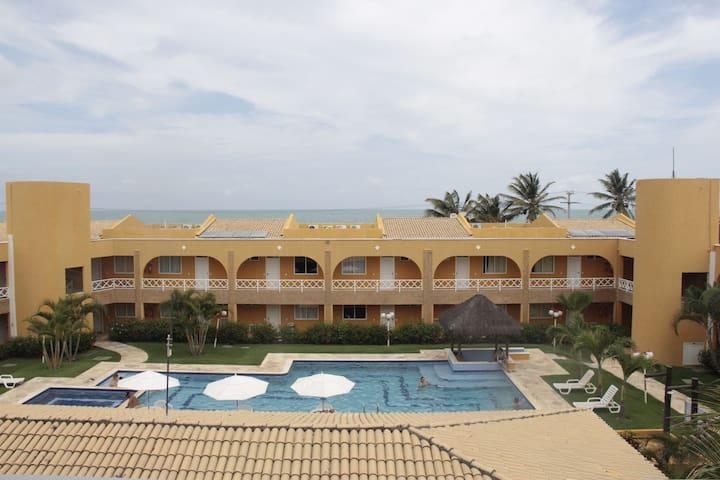 Varanda com vista para o mar e piscina.