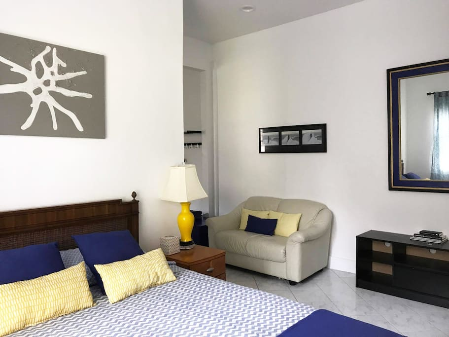 Next to the bedroom is a comfy couch perfect to lounge along side a mirror and an area to store your shoes and other belongings