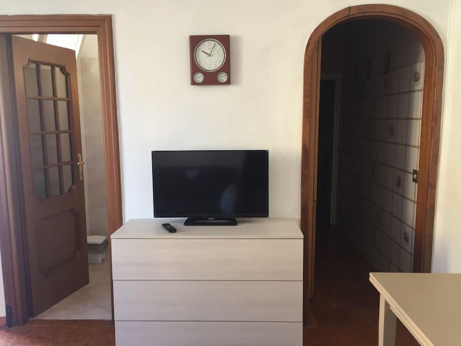 Sala con TV e a sinistra bagno a destra cucina