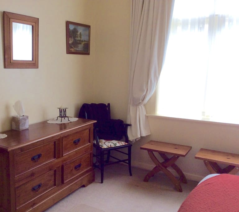 same room showing dresser and luggage  stands, also has a wardrobe
