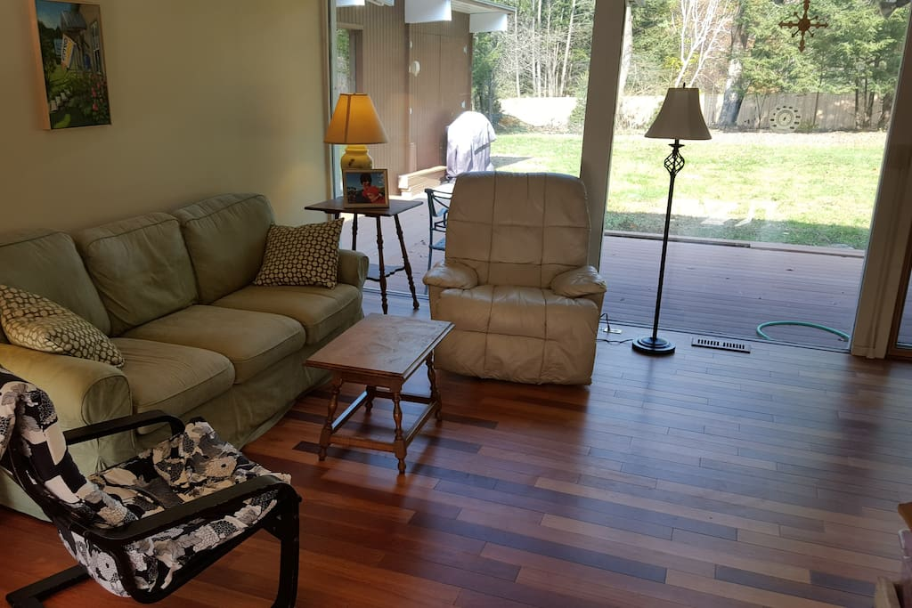 Sunlit living room opens to outside and deck.