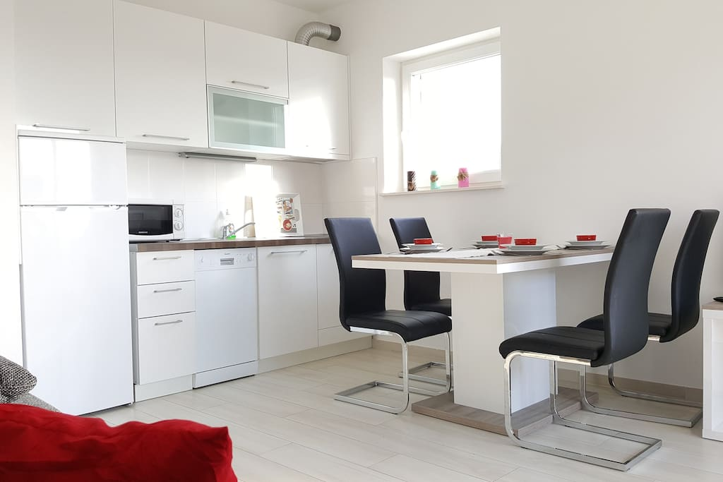 Fully equipped kitchen with living room. In kitchen is dining table and a sofa for two is in living room.