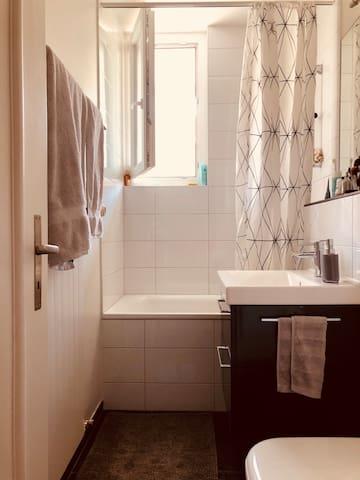 Shared bathroom with small bath tub and window