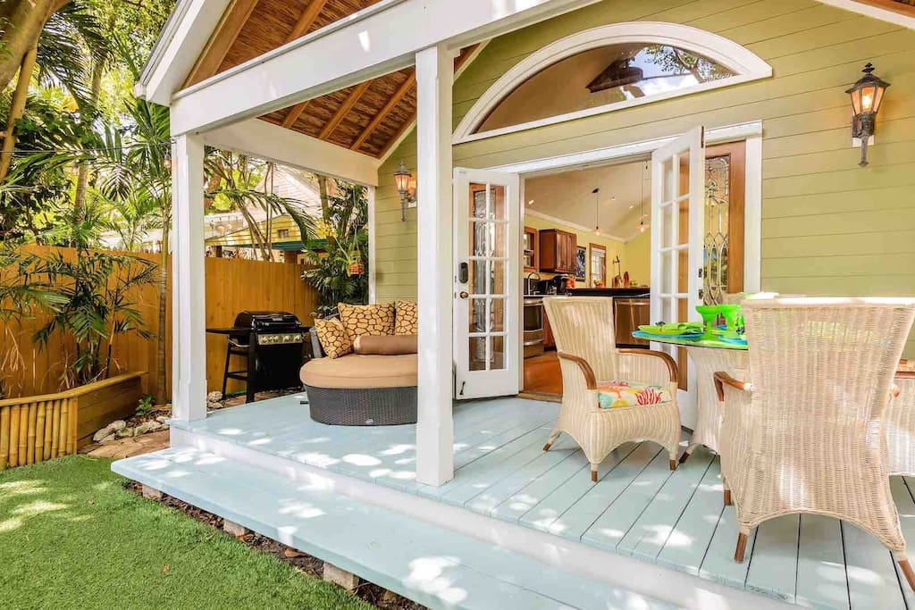 The covered back patio has an oversized lounger and outdoor dining set for four...