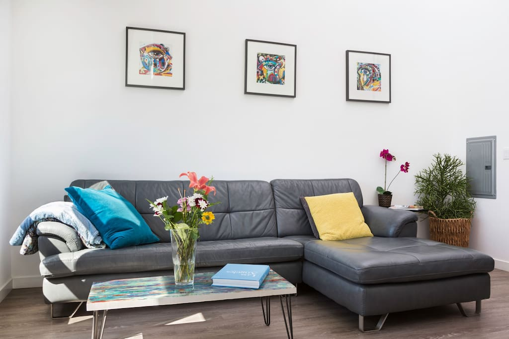 Original modern artwork fills the space throughout and a large soft couch makes for easy relaxing