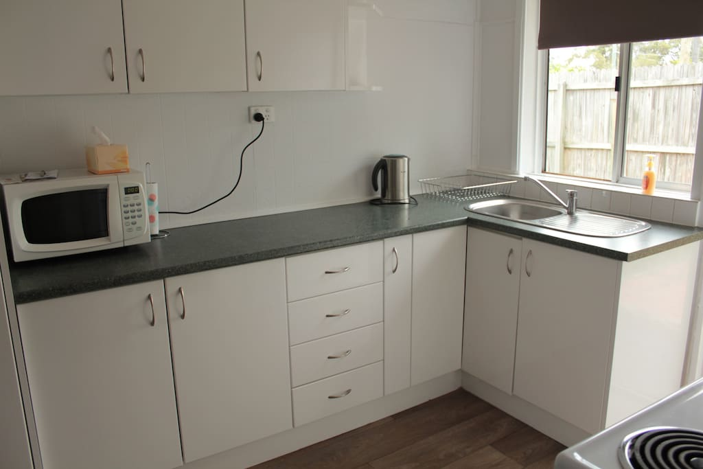 This kitchen is fully functional and includes a large fridge/freezer, plates, bowls, cups, glasses, pots and pans  as well as a growing range condiments for you convenience.