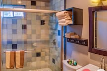 An oversized shower with all of he amenities you might need... including robes.