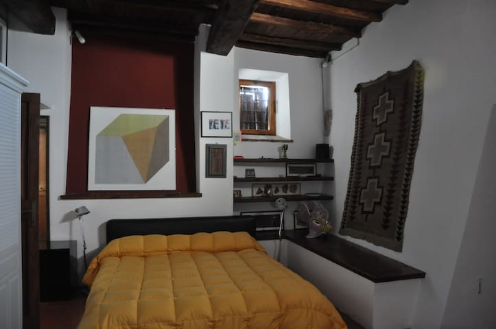 Large double bed in master bedroom opens to a stone terrace.